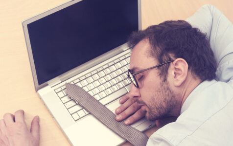 Businessman Sleeping on Laptop