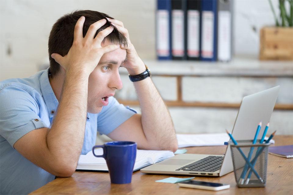 Man Looking at Laptop Worried