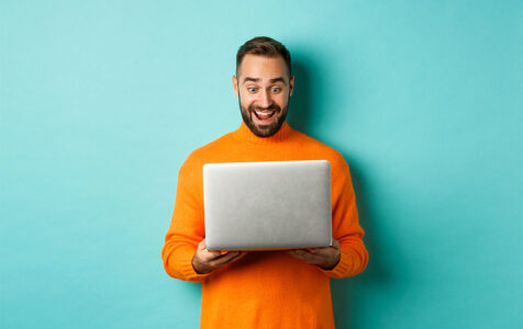 Excited Man in Orange Sweater Holding Laptop