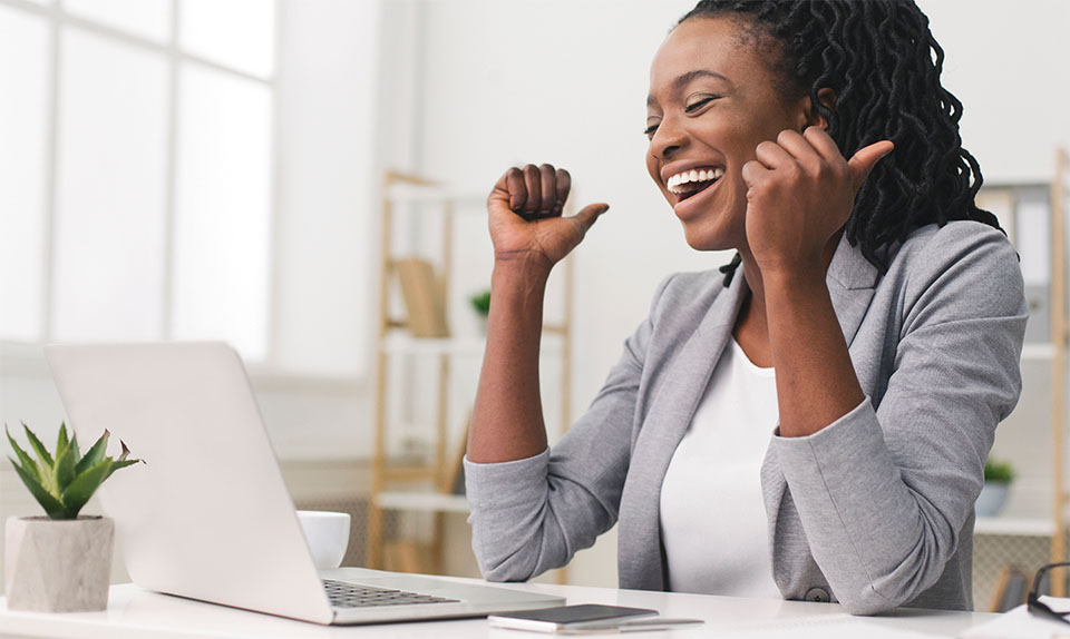 Happy African American Woman in Front of Laptop