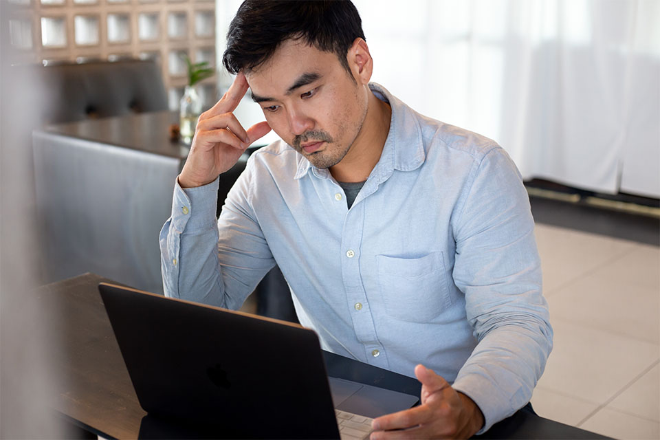 Asian Man Thinking in Front of Computer
