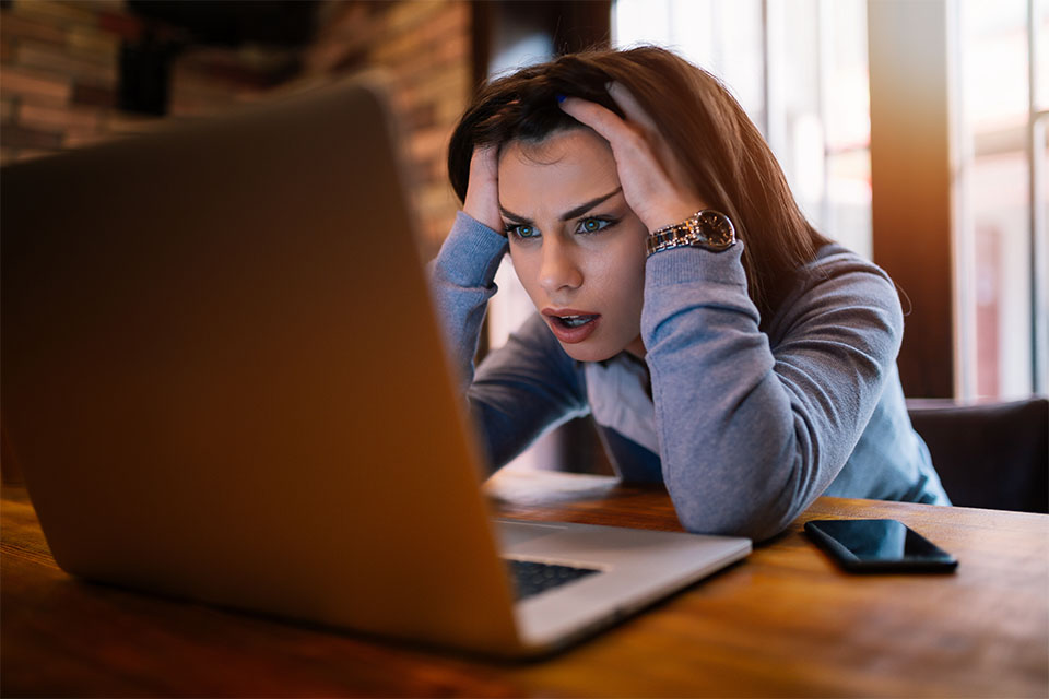 Frustrated Young Woman Looking at Laptop