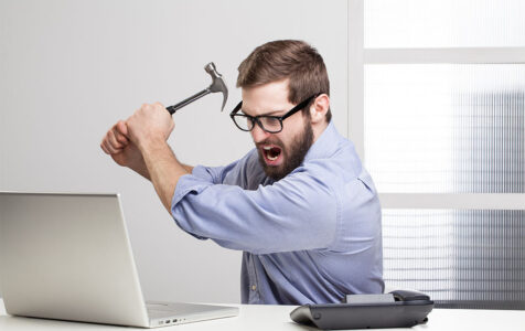 Man with Hammer in Front of Computer